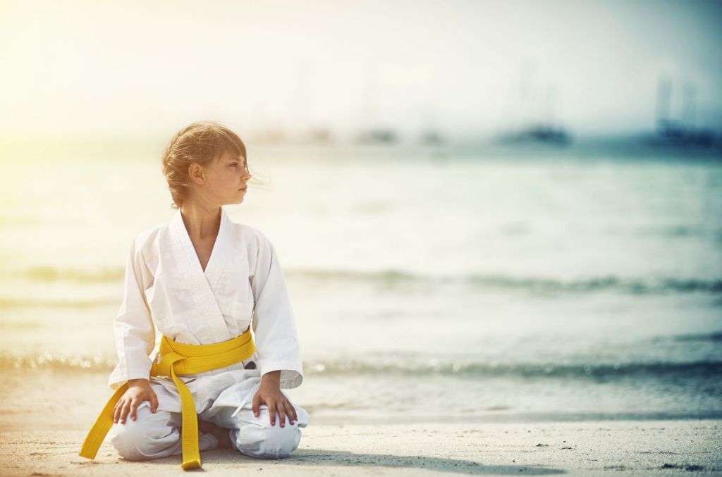 Kind im Karete-Anzug am Meer